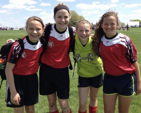 Seniors Alina Merlak, Sam White, Grace Krapfl, and Quinnie Rodman pose after an AYSO soccer game.
