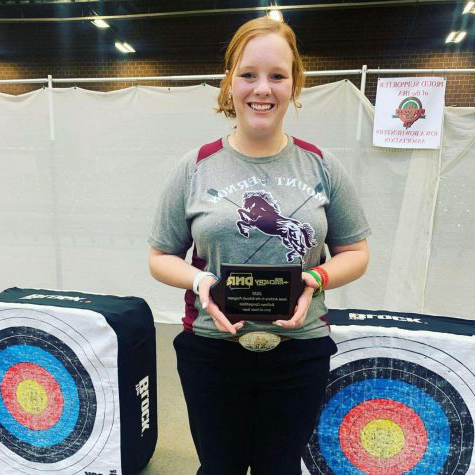 Senior Paige Emig smiles as she holds her award for placing fifth at state archery with a score of 290.