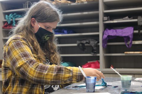 "Senior Quinn Alles pours paint onto a canvas in Art Media Survey Sept. 11. Alles used three different colors in her acrylic pour painting. ""That project was super fun."" Alles said, ""We got to experiment a lot with color schemes and ways to make different shades of colors."""